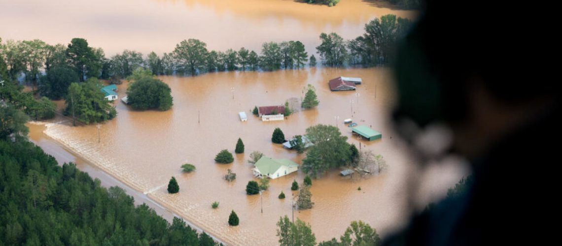 An official looks out a Blackhawk Helicopter at homes surrounded by flood waters due to Hurricane Florence in Conway, South Carolina. Many rivers in the Carolinas are approaching record flood stages and their levels will continue to rise through the week.